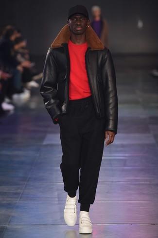 schwarze Lammfelljacke, roter Pullover mit einem Rundhalsausschnitt, schwarze Jogginghose, weiße Leder niedrige Sneakers für Herren