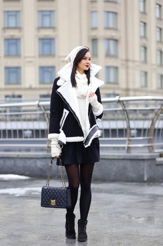 Wie kombinieren: schwarze und weiße Lammfelljacke, weißer Pullover mit einem Rundhalsausschnitt, schwarzer Skaterrock, schwarze flache Stiefel mit einer Schnürung aus Wildleder