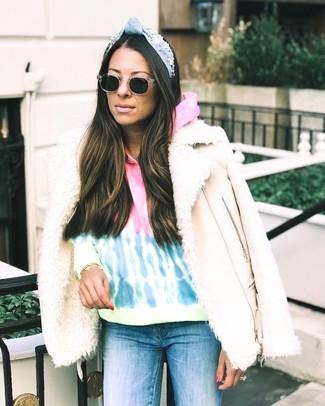 Wie kombinieren: hellbeige Lammfelljacke, mehrfarbiger Mit Batikmuster Pullover mit einer Kapuze, blaue enge Jeans, schwarze Sonnenbrille