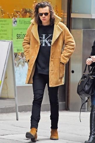 Harry Styles trägt Beige Lammfelljacke, Schwarzer bedruckter Pullover mit Rundhalsausschnitt, Schwarze Wollanzughose, Beige Chelsea-Stiefel aus Wildleder