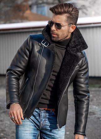 Wie kombinieren: schwarze Lammfelljacke, schwarzer Rollkragenpullover, blaue Jeans, rotbrauner geflochtener Ledergürtel