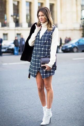 Wie kombinieren: schwarze Lammfelljacke, hellbeige Rollkragenpullover, dunkelblauer Kleiderrock mit Karomuster, weiße Leder Stiefeletten mit Ausschnitten