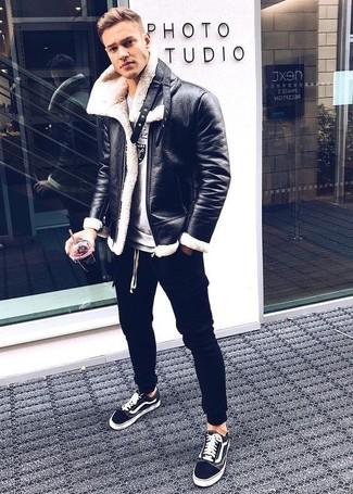 Wie kombinieren: schwarze Lammfelljacke, graues bedrucktes Sweatshirt, schwarze Jogginghose, schwarze niedrige Sneakers