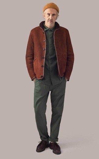 Winter Outfits Herren 2021: Tragen Sie eine braune Lammfelljacke und eine dunkelgrüne Chinohose für ein großartiges Wochenend-Outfit. Dieses Outfit passt hervorragend zusammen mit dunkelroten Chukka-Stiefeln aus Leder. Ein schönes Winter-Outfit.