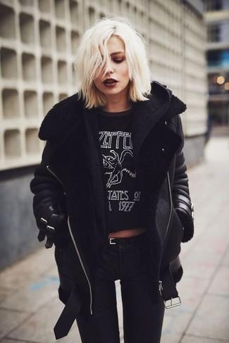 Wie kombinieren: schwarze Lammfelljacke, schwarze Strick Strickjacke, schwarzes und weißes bedrucktes T-Shirt mit einem Rundhalsausschnitt, schwarze enge Jeans
