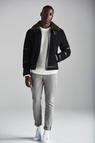 Wie kombinieren: schwarze Lammfelljacke, weißer Strickpullover, graue Chinohose, weiße Leder niedrige Sneakers