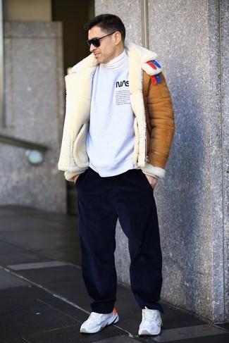 Wie kombinieren: rotbraune Lammfelljacke, weißes und schwarzes bedrucktes Sweatshirt, weißer Rollkragenpullover, dunkelblaue Cord Chinohose