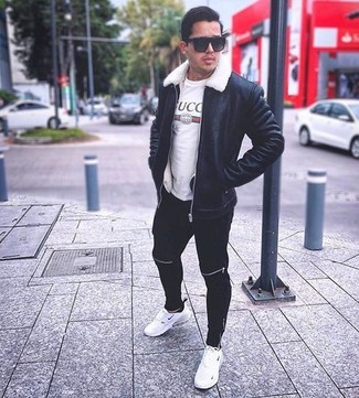 Wie kombinieren: schwarze Lammfelljacke, weißes bedrucktes T-Shirt mit einem Rundhalsausschnitt, schwarze Jogginghose, weiße Sportschuhe