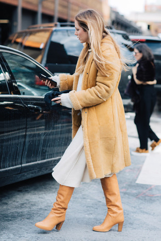 Wie kombinieren: beige Lammfellmantel, weißer Oversize Pullover, weißer Wollmidirock, beige kniehohe Stiefel aus Leder