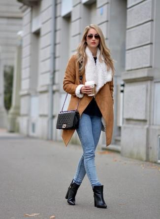 Wie kombinieren: beige Lammfellmantel, schwarze Langarmbluse, hellblaue enge Jeans, schwarze Leder Stiefeletten
