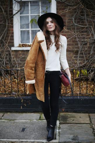 Wie kombinieren: beige Lammfellmantel, weißer Pullover mit einem Rundhalsausschnitt, schwarze enge Jeans, schwarze Leder Stiefeletten