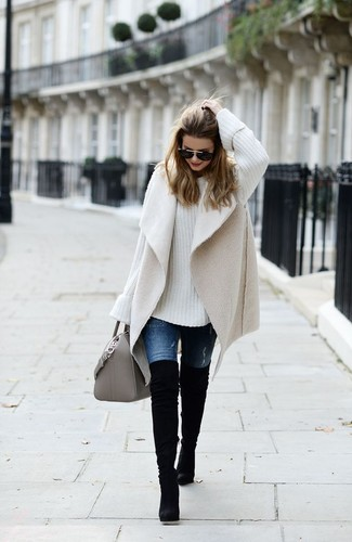 Wie kombinieren: hellbeige Lammfellweste, weißer Strick Oversize Pullover, blaue Jeans, schwarze Overknee Stiefel aus Wildleder