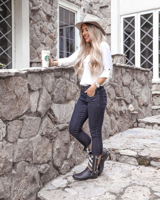 Wie kombinieren: weiße Langarmbluse, dunkelblaue enge Jeans, schwarze Gummistiefel mit Schottenmuster, grauer Wollhut