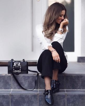Wie kombinieren: weiße Langarmbluse, schwarze Karottenhose, schwarze Fransen Leder Slipper, schwarze verzierte Leder Umhängetasche