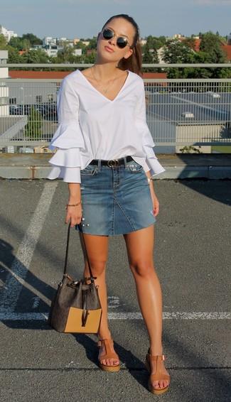 Wie kombinieren: weiße Langarmbluse mit Rüschen, blauer Jeans Minirock, beige Keilsandaletten aus Leder, dunkelbraune Leder Beuteltasche