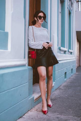 Wie kombinieren: weiße und schwarze gepunktete Langarmbluse, schwarzer Falten Leder Minirock, rote Leder Pumps, rote Leder Umhängetasche