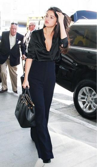 Selena Gomez trägt schwarze Satin Langarmbluse, dunkelblaue weite Hose, schwarze Leder Pumps, schwarze Shopper Tasche aus Leder