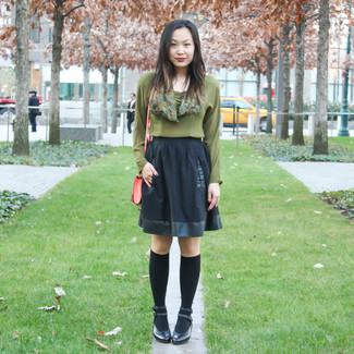 Wie kombinieren: olivgrüne Langarmbluse, schwarzer Skaterrock, schwarze Leder Pumps, schwarze hohe Socken