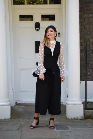 Wie kombinieren: weiße gepunktete Langarmbluse, schwarzer Jumpsuit, schwarze Wildleder Sandaletten, schwarze Ohrringe