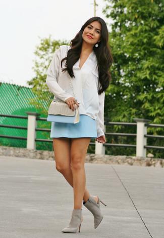 Wie kombinieren: weiße Seide Langarmbluse, hellblauer Minirock, graue Wildleder Stiefeletten mit Ausschnitten, hellblaue Leder Umhängetasche