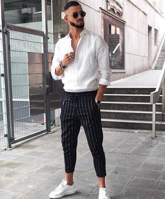 Wie kombinieren: weißes Leinen Langarmhemd, schwarze vertikal gestreifte Anzughose, weiße Leder niedrige Sneakers, schwarze Sonnenbrille