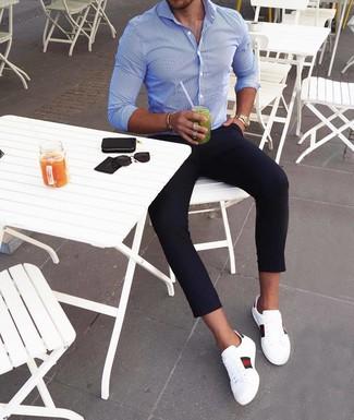 Wie kombinieren: blaues vertikal gestreiftes Langarmhemd, dunkelblaue Chinohose, weiße bedruckte Leder niedrige Sneakers, goldene Uhr