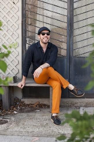 Wie kombinieren: schwarzes Langarmhemd, orange Chinohose, schwarze Leder Bootsschuhe, schwarze Schiebermütze