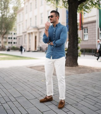Wie kombinieren: blaues Chambray Langarmhemd, weiße Chinohose, braune Wildleder Bootsschuhe, schwarze Sonnenbrille