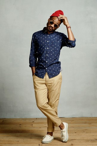 Wie kombinieren: dunkelblaues bedrucktes Langarmhemd, beige Chinohose, weiße Segeltuch niedrige Sneakers, rote Mütze