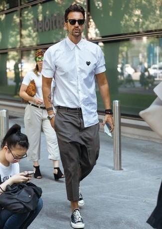 Herren Outfits & Modetrends 2020: Erwägen Sie das Tragen von einem weißen und schwarzen bedruckten Langarmhemd und einer dunkelgrauen Chinohose, um mühelos alles zu meistern, was auch immer der Tag bringen mag. Schwarze und weiße Segeltuch niedrige Sneakers sind eine ideale Wahl, um dieses Outfit zu vervollständigen.