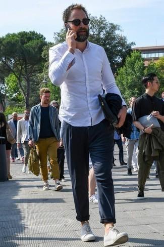 Dunkelblaue Segeltuch Clutch Handtasche kombinieren: trends 2020: Erwägen Sie das Tragen von einem weißen Langarmhemd und einer dunkelblauen Segeltuch Clutch Handtasche für einen entspannten Wochenend-Look. Setzen Sie bei den Schuhen auf die klassische Variante mit weißen Segeltuch niedrigen Sneakers.