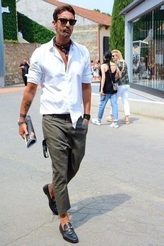 Herren Outfits & Modetrends 2020: Arbeitsreiche Tage verlangen nach einem einfachen, aber dennoch stylischen Outfit, wie zum Beispiel ein weißes Langarmhemd und eine dunkelgrüne Chinohose. Machen Sie Ihr Outfit mit schwarzen Leder Slippern eleganter.