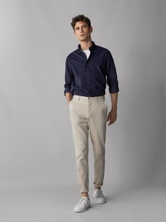 Hellbeige Chinohose kombinieren: trends 2020: Erwägen Sie das Tragen von einem dunkelblauen Langarmhemd und einer hellbeige Chinohose, um mühelos alles zu meistern, was auch immer der Tag bringen mag. Wählen Sie die legere Option mit weißen niedrigen Sneakers.
