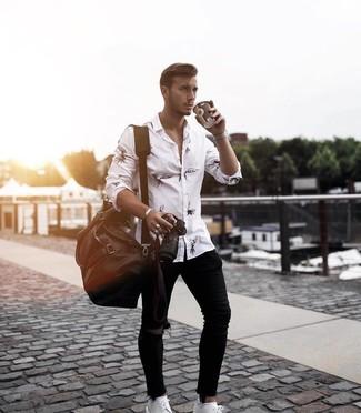 Wie kombinieren: weißes und schwarzes bedrucktes Langarmhemd, schwarze enge Jeans mit Destroyed-Effekten, weiße Leder Derby Schuhe, dunkelbraune Leder Reisetasche