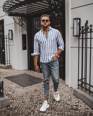 Wie kombinieren: weißes und blaues vertikal gestreiftes Langarmhemd, blaue enge Jeans mit Destroyed-Effekten, weiße und schwarze Leder niedrige Sneakers, schwarze Sonnenbrille