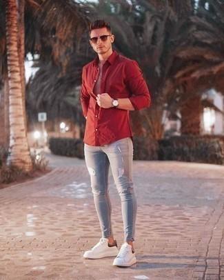 Weiße und schwarze Leder niedrige Sneakers kombinieren: trends 2020: Für ein bequemes Couch-Outfit, paaren Sie ein rotes Langarmhemd mit grauen engen Jeans mit Destroyed-Effekten. Heben Sie dieses Ensemble mit weißen und schwarzen Leder niedrigen Sneakers hervor.