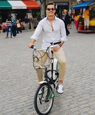 Wie kombinieren: hellblaues vertikal gestreiftes Langarmhemd, beige enge Jeans, weiße und schwarze niedrige Sneakers, dunkelbraune Sonnenbrille