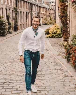 Wie kombinieren: weißes Leinen Langarmhemd, blaue Jeans, weiße Segeltuch niedrige Sneakers, blauer Bandana mit Paisley-Muster