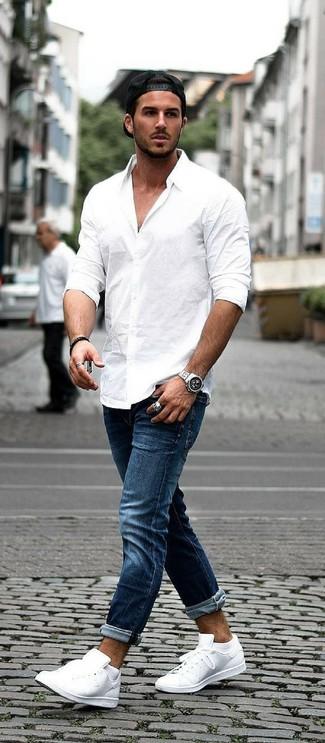 Wie kombinieren: weißes Langarmhemd, dunkelblaue Jeans, weiße Leder niedrige Sneakers, schwarze Baseballkappe