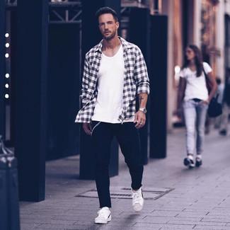 Wie kombinieren: schwarzes und weißes Flanell Langarmhemd mit Schottenmuster, weißes Trägershirt, schwarze Jeans, weiße und schwarze Leder niedrige Sneakers