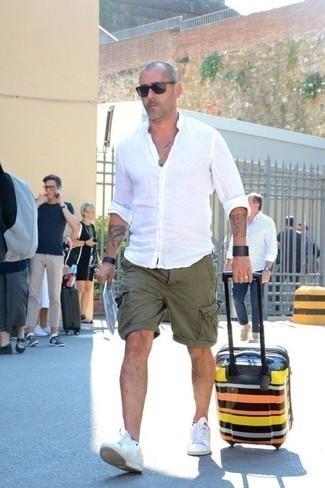 Weiße Leder niedrige Sneakers kombinieren: Casual-Outfits: trends 2020: Kombinieren Sie ein weißes Leinen Langarmhemd mit olivgrünen Shorts, um mühelos alles zu meistern, was auch immer der Tag bringen mag. Weiße Leder niedrige Sneakers sind eine kluge Wahl, um dieses Outfit zu vervollständigen.