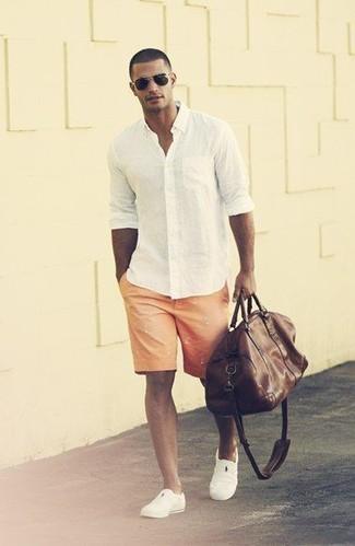 Wie kombinieren: weißes Langarmhemd, orange bedruckte Shorts, weiße Slip-On Sneakers, dunkelbraune Leder Sporttasche