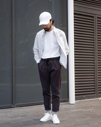 Weißes vertikal gestreiftes Langarmhemd kombinieren: trends 2020: Erwägen Sie das Tragen von einem weißen vertikal gestreiften Langarmhemd und einer schwarzen vertikal gestreiften Chinohose für ein großartiges Wochenend-Outfit. Weiße Leder niedrige Sneakers sind eine perfekte Wahl, um dieses Outfit zu vervollständigen.