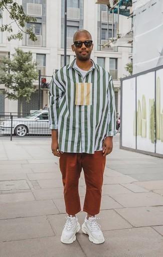 Herren Outfits 2020: Vereinigen Sie ein weißes und grünes vertikal gestreiftes Langarmhemd mit einer rotbraunen Chinohose für ein bequemes Outfit, das außerdem gut zusammen passt. Fühlen Sie sich mutig? Vervollständigen Sie Ihr Outfit mit weißen Sportschuhen.