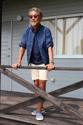 Hellbeige Leinen Shorts kombinieren – 4 Herren Outfits: Die Kombination von einem blauen Chambray Langarmhemd und hellbeige Leinen Shorts erlaubt es Ihnen, Ihren Freizeitstil klar und einfach zu halten. Ergänzen Sie Ihr Look mit hellblauen Slip-On Sneakers.