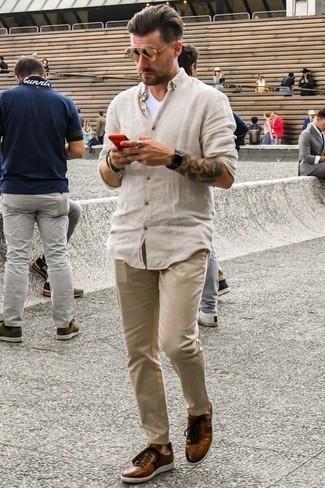 Goldene Sonnenbrille kombinieren: trends 2020: Tragen Sie ein hellbeige Leinen Langarmhemd und eine goldene Sonnenbrille für einen entspannten Wochenend-Look. Vervollständigen Sie Ihr Outfit mit rotbraunen Leder niedrigen Sneakers, um Ihr Modebewusstsein zu zeigen.