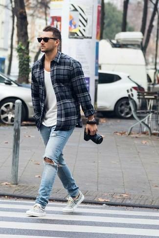 Wie blaue enge Jeans mit Destroyed Effekten mit Flanell