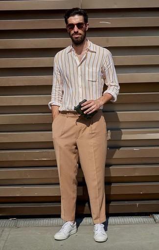 Weißes vertikal gestreiftes Langarmhemd kombinieren: trends 2020: Kombinieren Sie ein weißes vertikal gestreiftes Langarmhemd mit einer beige Chinohose für ein sonntägliches Mittagessen mit Freunden. Vervollständigen Sie Ihr Look mit weißen Leder niedrigen Sneakers.
