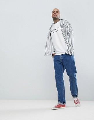 Wie kombinieren: weißes und schwarzes vertikal gestreiftes Langarmhemd, weißes und schwarzes bedrucktes T-Shirt mit einem Rundhalsausschnitt, blaue Jeans, rote Segeltuch niedrige Sneakers