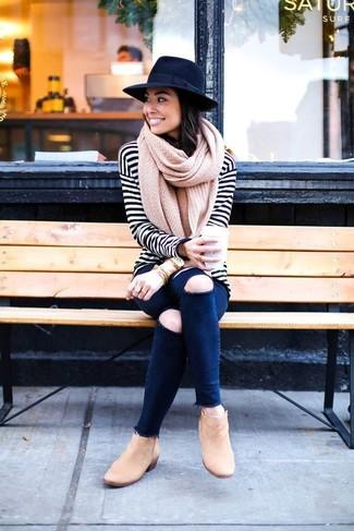 Wie kombinieren: weißes und schwarzes horizontal gestreiftes Langarmshirt, dunkelblaue enge Jeans mit Destroyed-Effekten, beige Wildleder Stiefeletten, schwarzer Wollhut